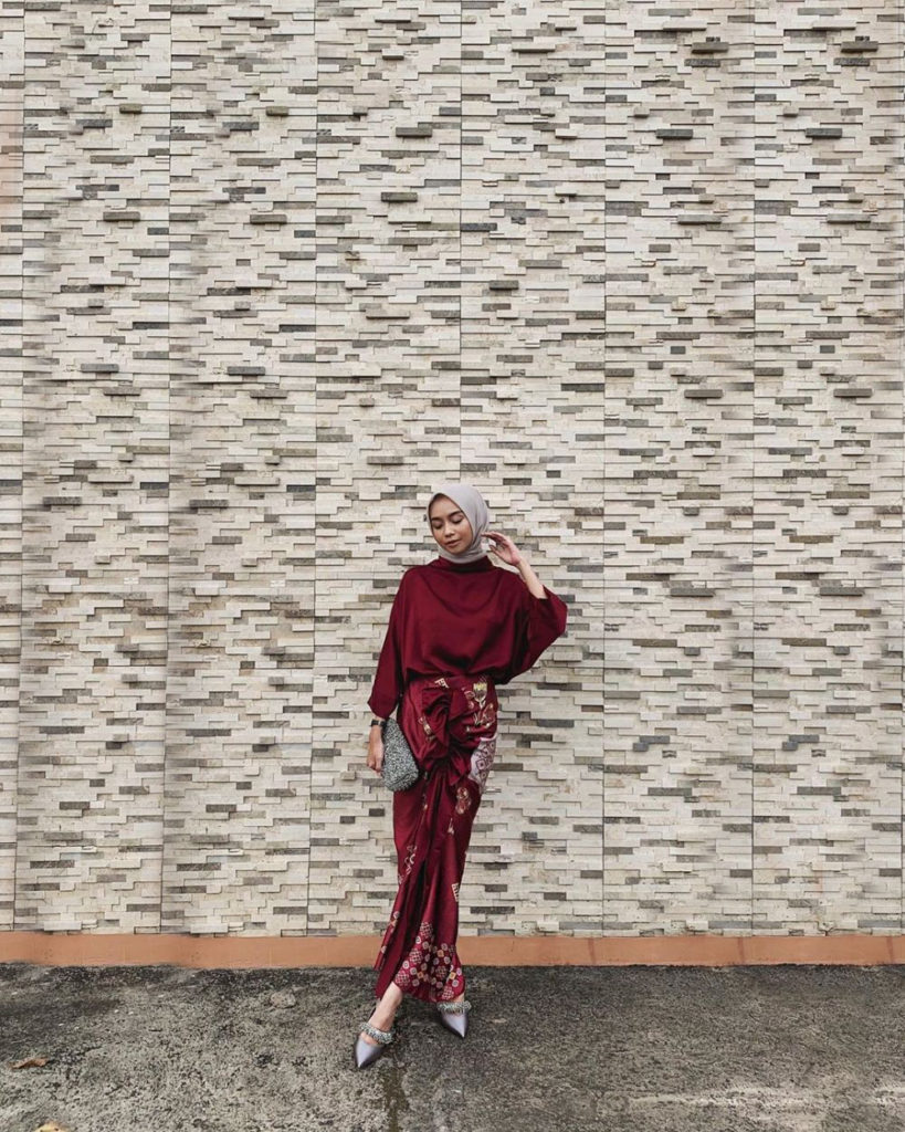 Cewek manis Pose beridri pakai Sarung dan HIjab di depan dinding