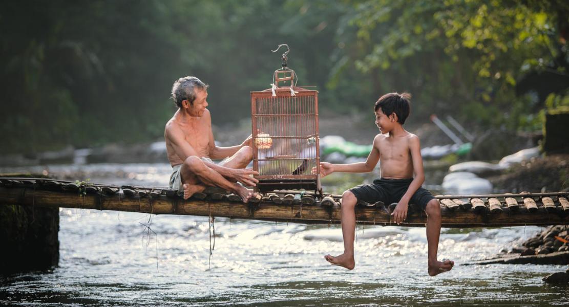 Foto Human Insterest Kakek di sebuah Jemtana di Atas sungai main burung dengan cucunya